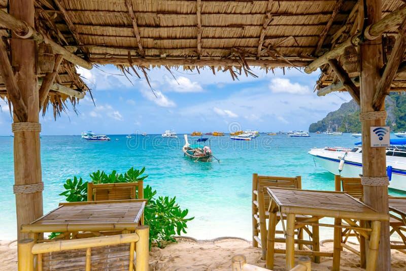 Restaurante tailandês em uma praia tropical com tabelas e palha de madeira fotos de stock royalty free