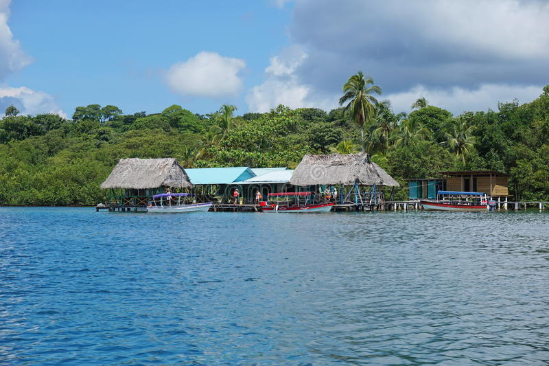 Restaurante tropical sobre o mar com o barco na doca imagem de stock royalty free