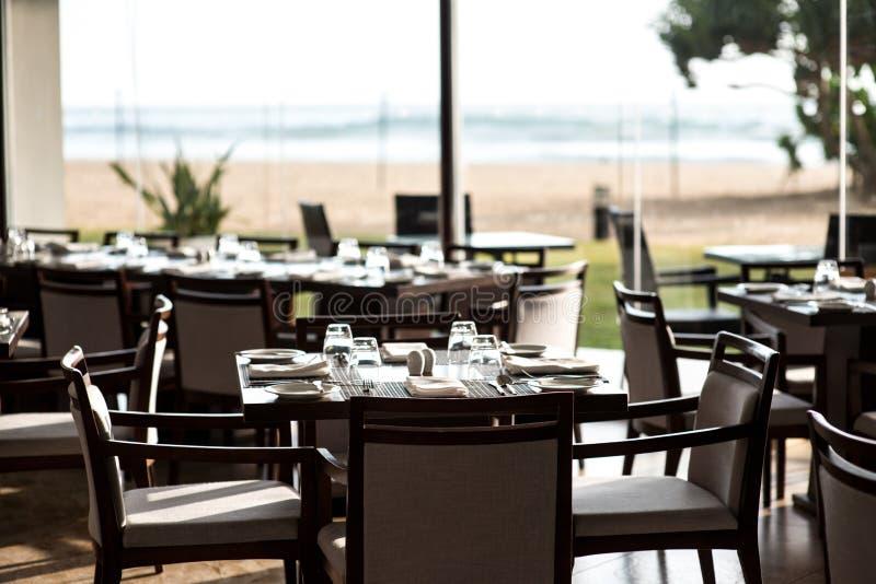 Restaurante vacío con las tablas servidas foto de archivo