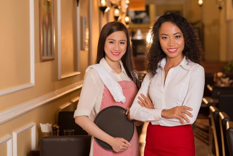 Restauranteigenaar en serveerster stock afbeelding