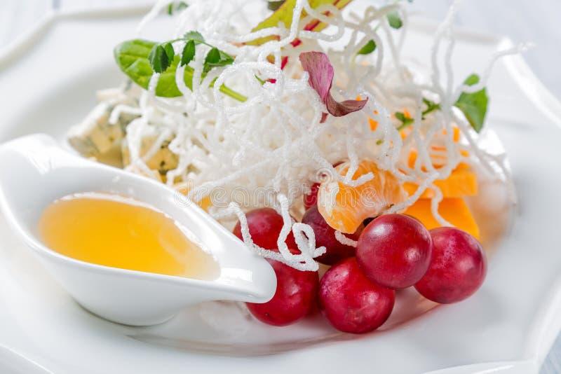 Restaurantkäseplatte - verschiedene Arten von Käsen mit Trauben, Walnuss und Tangerine mit Chips auf weißer Platte Schließen Sie  lizenzfreies stockbild