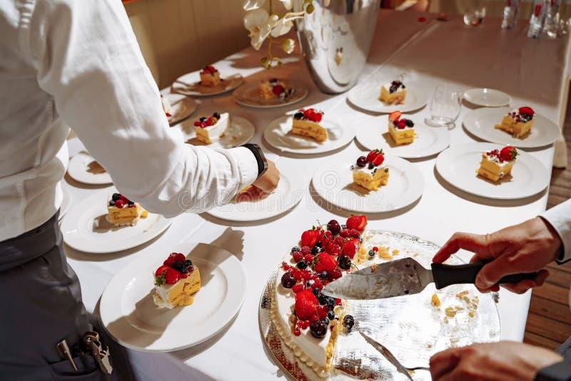 Restaurantkellner, die süßen Kuchen in Stücke für dienende Gäste am Feiertag schneiden Hände schließen herauf Ansicht lizenzfreie stockfotografie