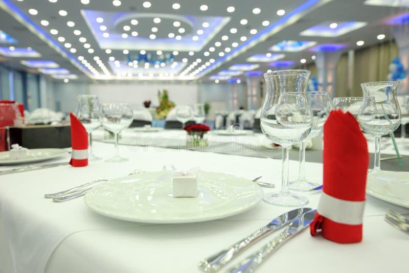 Restaurantlijst met plaat, wijnglas en bestek stock afbeeldingen