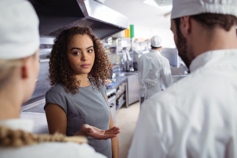 Restaurantmanager, der auf sein Küchenpersonal einwirkt stockfotografie