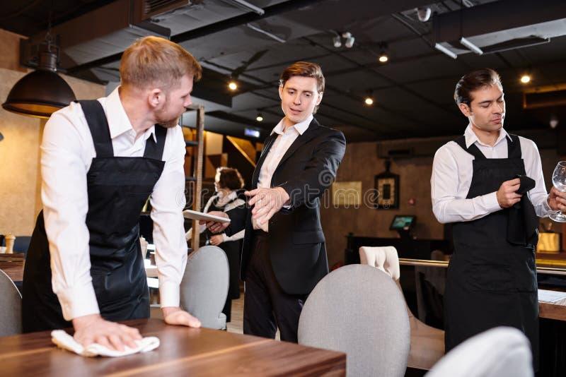 Restaurantmanager, der dem Kellner Aufgabe während der Reinigung gibt stockfotos
