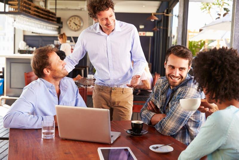 Restaurantmanager, der mit Kunden an ihrem Tisch spricht lizenzfreies stockbild
