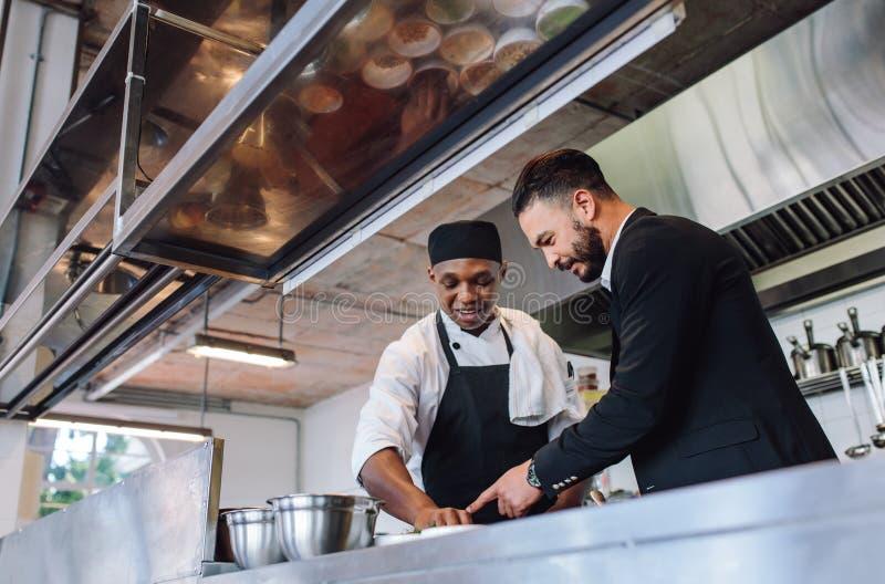Restaurantmanager met chef-kok in keuken stock afbeeldingen