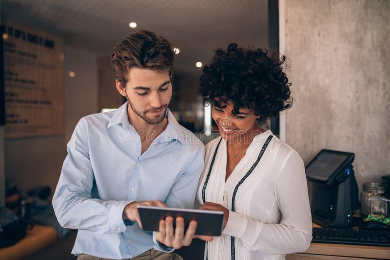 Restaurantpartners die digitale tablet gebruiken stock foto