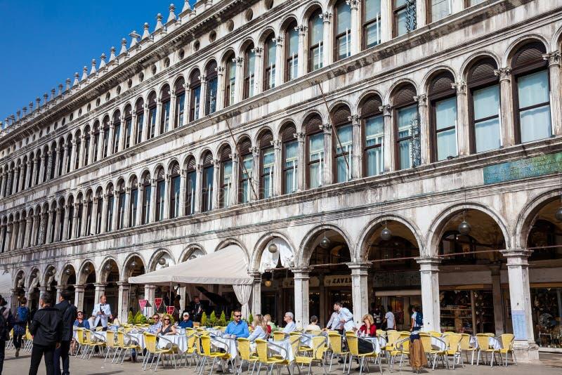 Restaurants en toeristen in de beroemde Heilige Mark Square van Venetië in de mooie zonnige vroege lente stock afbeeldingen