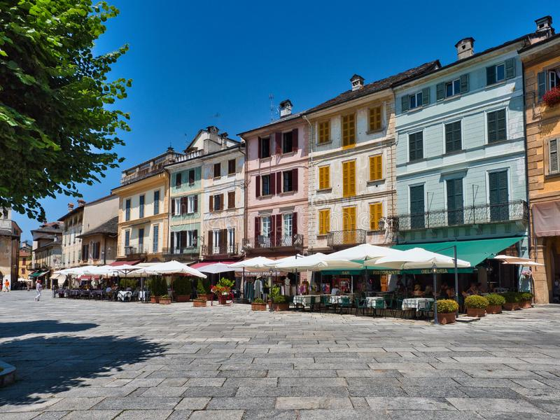 Restaurants and local businesses in Piazza Motta in the village of Orta San Giulio italy during a summer morning. Orta San Giulio, Lake Orta, Italy - June 29 royalty free stock photo