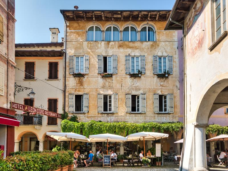 Restaurants at Piazza Motta in Orta San Giulio at Orta Lake in Italy being visited by tourists during a summer afternoon stock photography