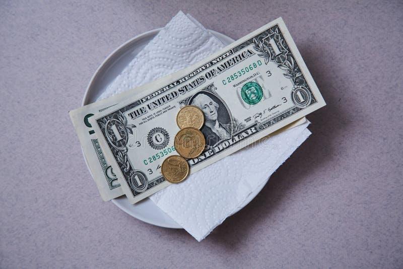 Restaurantspitzen oder -gratifikation Banknoten und Münzen auf einer Platte lizenzfreies stockbild