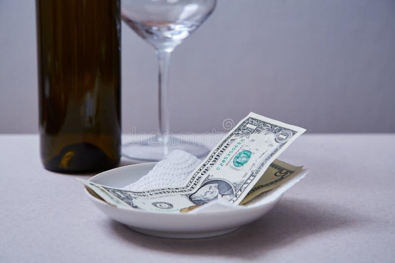 Restaurantspitzen oder -gratifikation Banknoten und Münzen auf einer Platte stockbilder