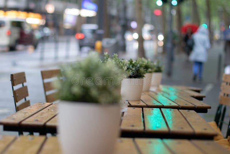 Restauranttabellen und -stühle im Regen lizenzfreie stockbilder