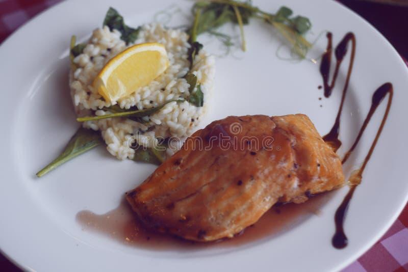 restaurantvoer Zalm met risotto Vissen en rijstvissen met citroen Schotel in het restaurant genaturaliseerd stock afbeeldingen