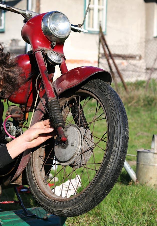 Restauratie rode ouderwetse motorfiets Jong van de teenageerreparaties geroest wiel en rem defect Typische Tsjechische rode motor stock fotografie