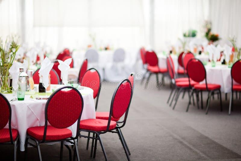 Restauration simple dans la réception de tente, chaises rouges, fond blanc photo libre de droits