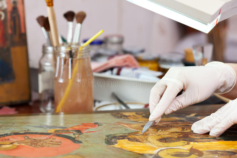 Restaurator som arbetar på den forntida kristna symbolen arkivbild
