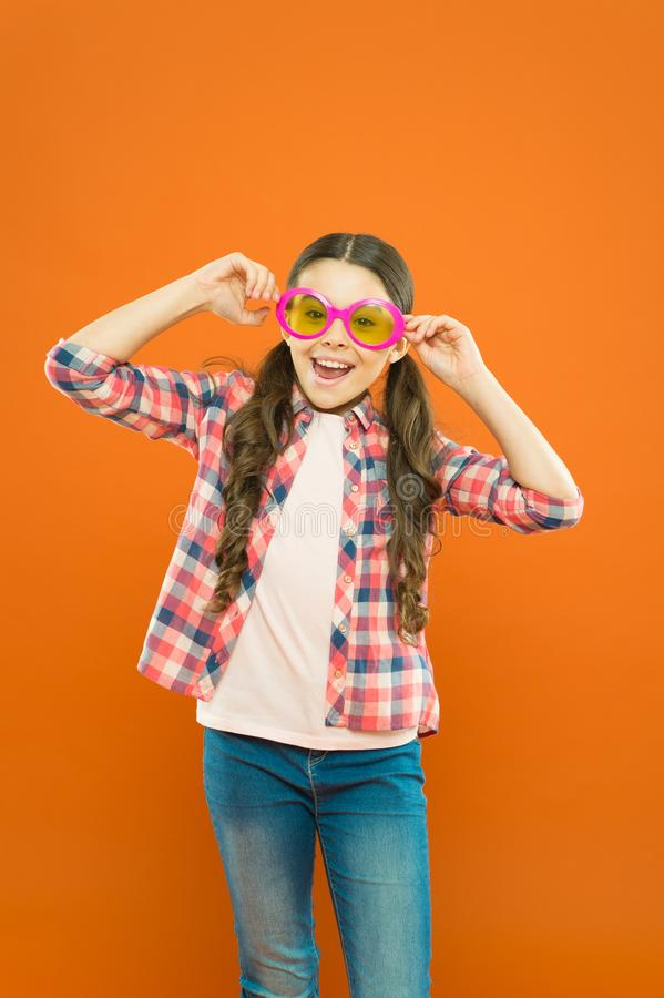 Rester focalisé avec des verres Petit enfant souriant avec des verres de partie de fantaisie sur le fond orange Le soleil de port photo libre de droits