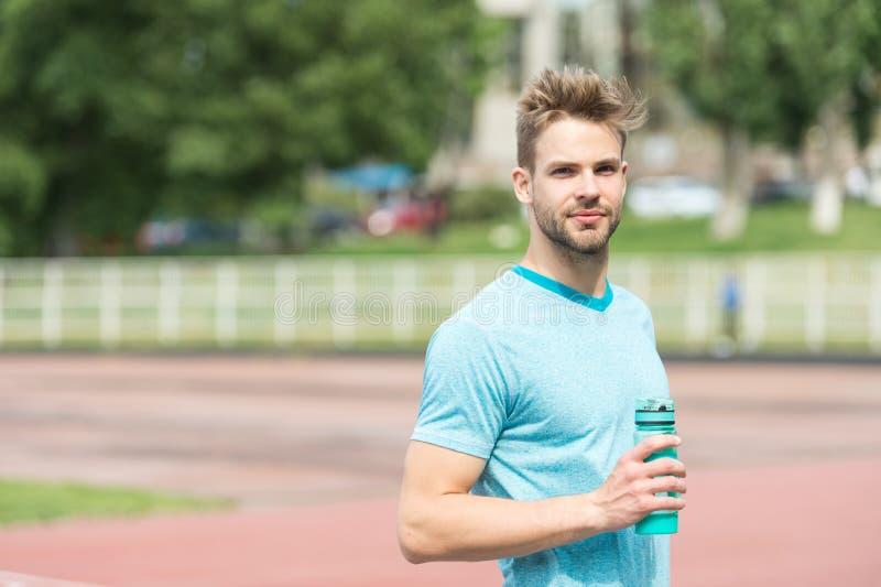 rester hydraté L'aspect sportif d'homme tient la bouteille d'eau continuent à rester hydraté pendant la formation Vêtements de sp image stock