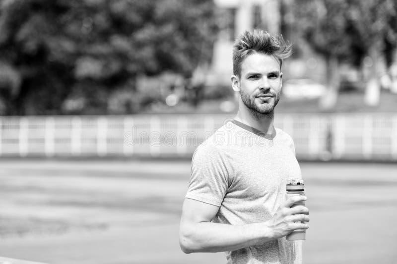 rester hydraté L'aspect sportif d'homme tient la bouteille d'eau continuent à rester hydraté pendant la formation Vêtements de sp photo stock
