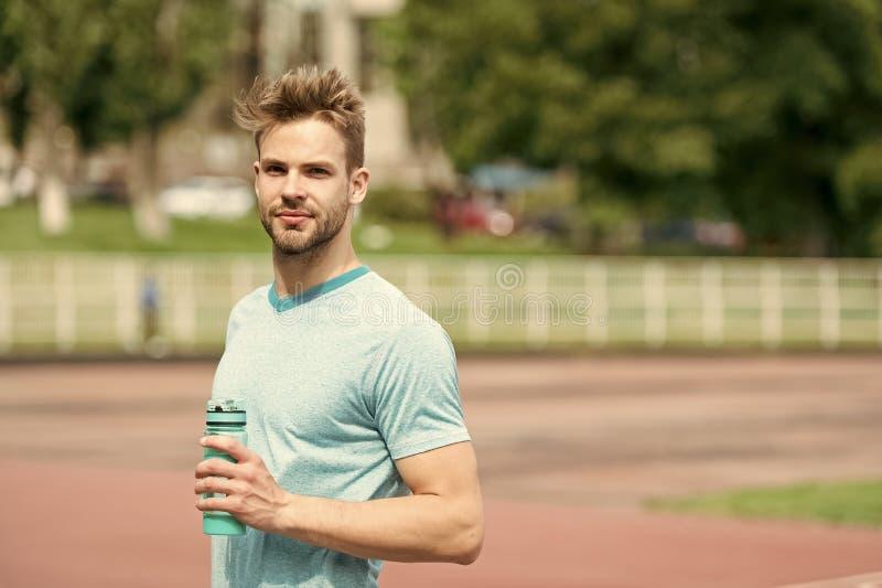 rester hydraté L'aspect sportif d'homme tient la bouteille d'eau continuent à rester hydraté pendant la formation Vêtements de sp photos stock