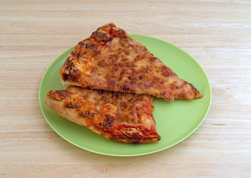 Rester ostpizza på en grön platta uppe på den wood tabellen arkivbild