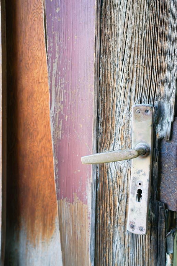 Restes de vieille poignée de porte et de levier avec les panneaux en bois superficiels par les agents photos libres de droits