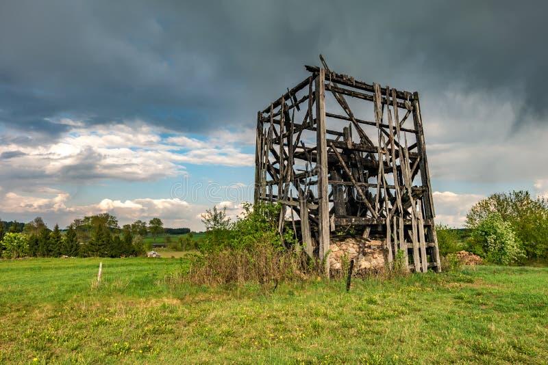Restes de vieux moulin ? vent br?l? dans le domaine avant la pluie image stock