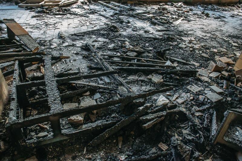 Restes des meubles en bois brûlés sur le plancher du bâtiment après le feu image stock