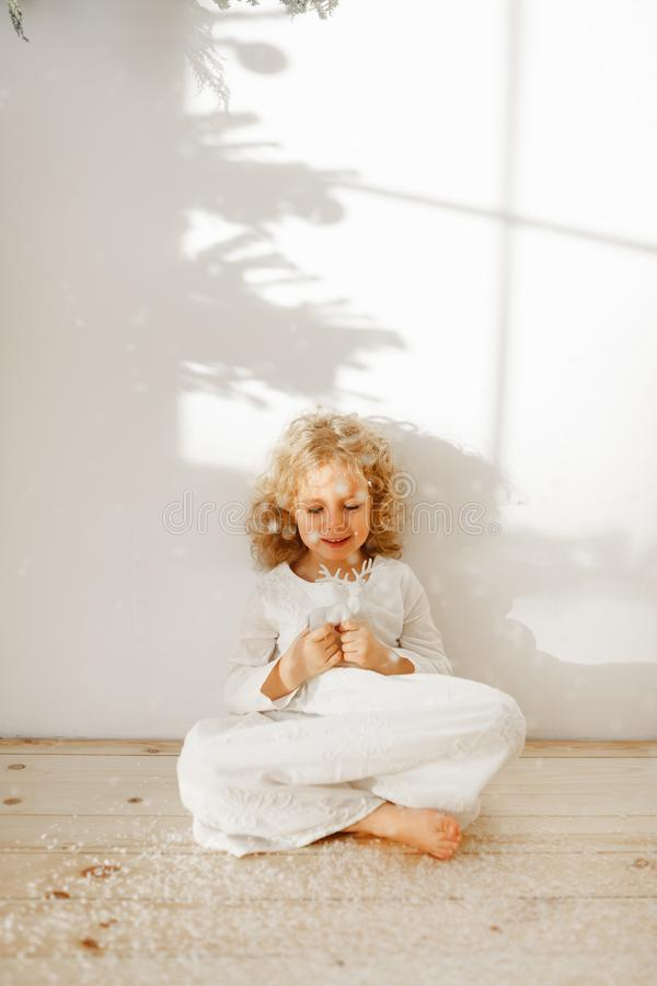 Restful adorable small kid dressed in long white dress, plays with Christmas toy deer, sits crossed legs on wooden floor. Over white studio background. Happy stock photo