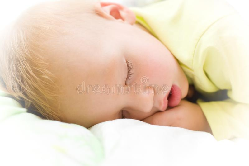 Restful baby boy sleeping on bed stock photos