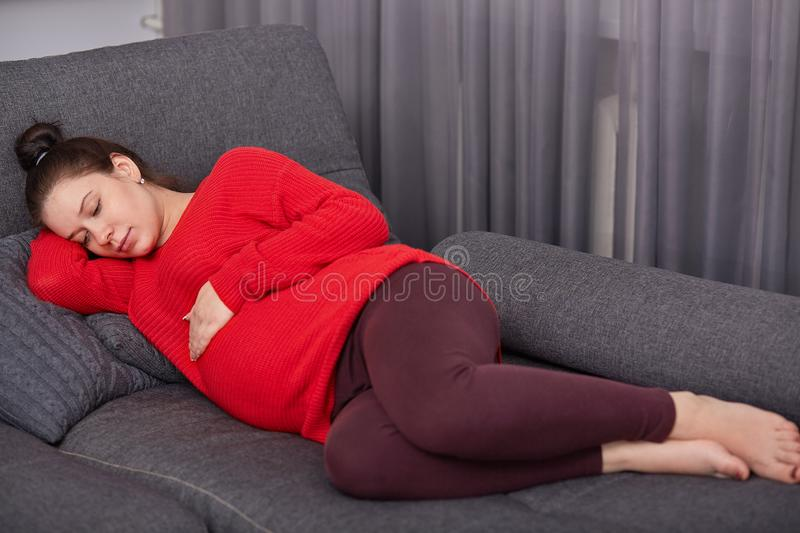 Restful European woman in red jumper and leggings, lies barefoot on couch, keeps hand on swollen tummy, going to become mother in. Future, has sleepy expression stock photo