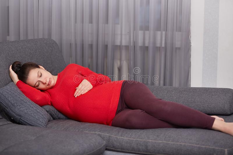 Restful young European woman wears red knitted sweater, leggings, lies on comfortable sofa, keeps hands on belly, anticipates for. Child, has thoughtful facial royalty free stock image