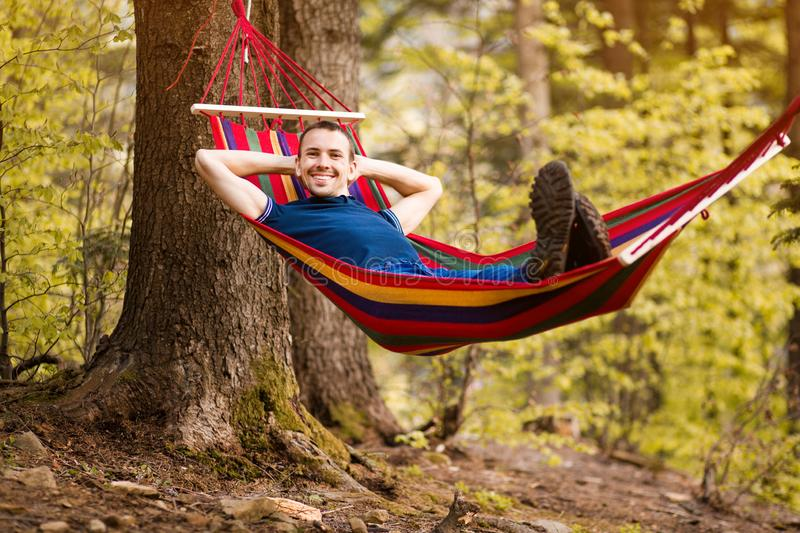 Restful young man laying down on hammock in middle of forest at park. Concept of dreaming, wellbeing and healthy lifes royalty free stock photos