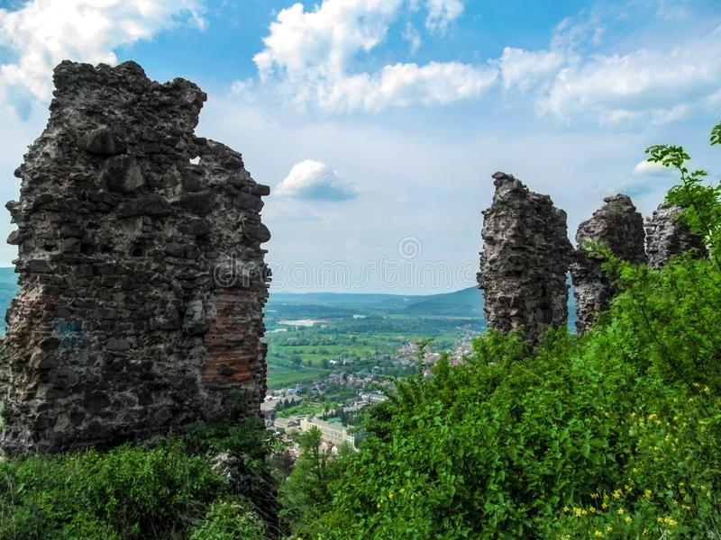 Resti imbronciato grigio delle pareti della fortezza antica contro lo sfondo del paesaggio della montagna in Khust Ucraina fotografia stock libera da diritti