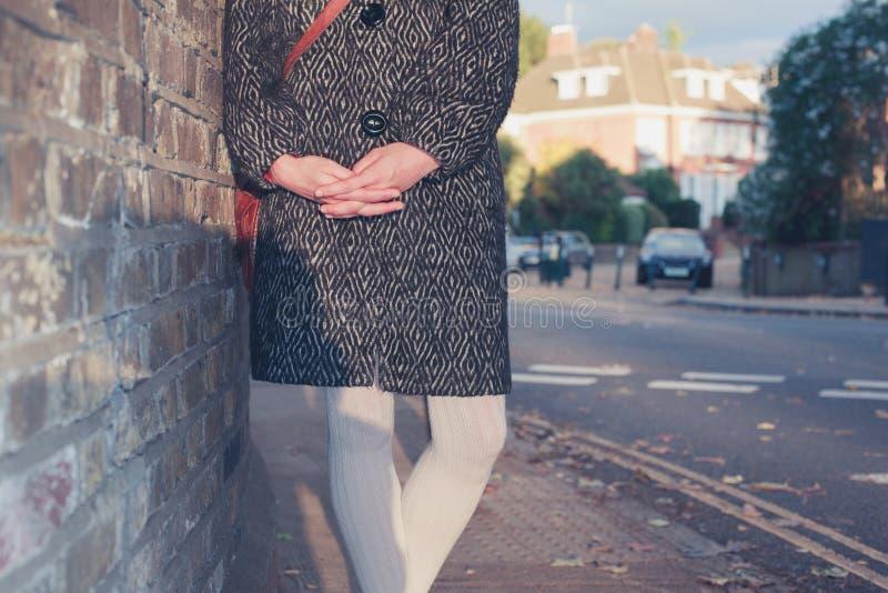 Restin da mulher contra a parede no por do sol fotos de stock