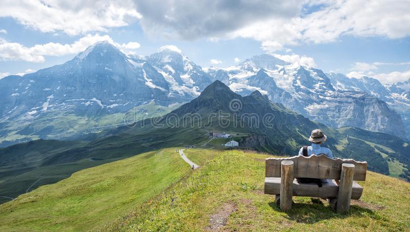 Resting at bench mannlichen mountain, view to famous peaks eiger. Mountaineer resting at wooden bench, enjoying the view to eiger, monch and jungfrau. famous stock image