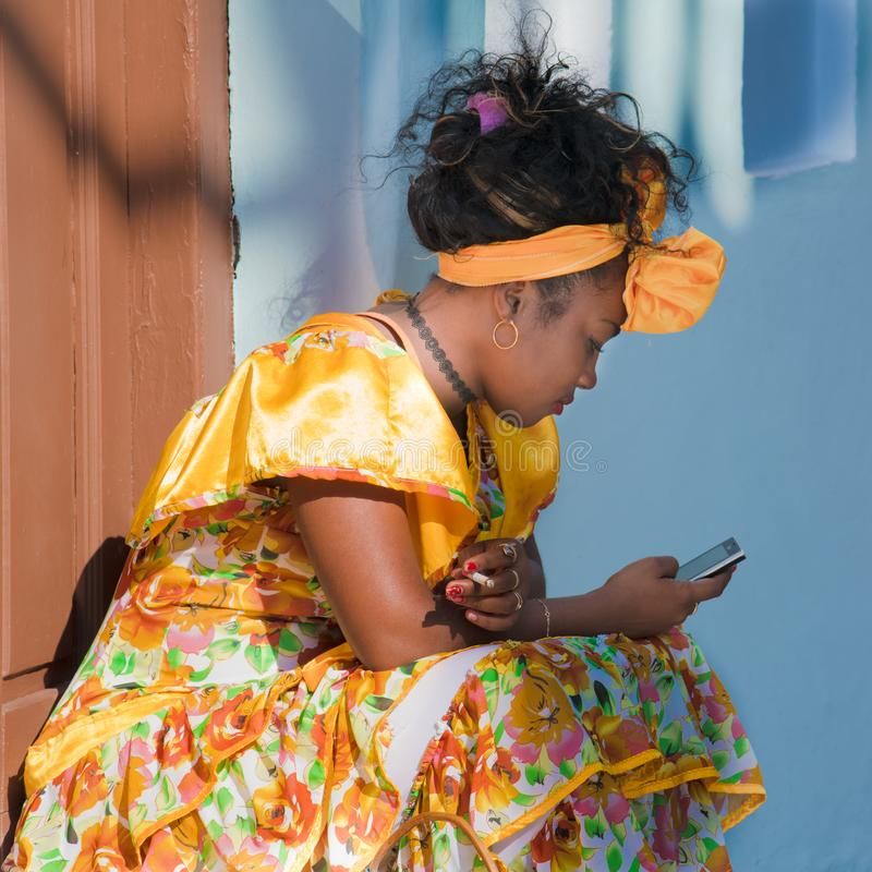 Cuban woman in typical costume, Havana, Habana Vieja, Cuba. Resting Cuban flower woman in typical dress and hair accessoires stock images