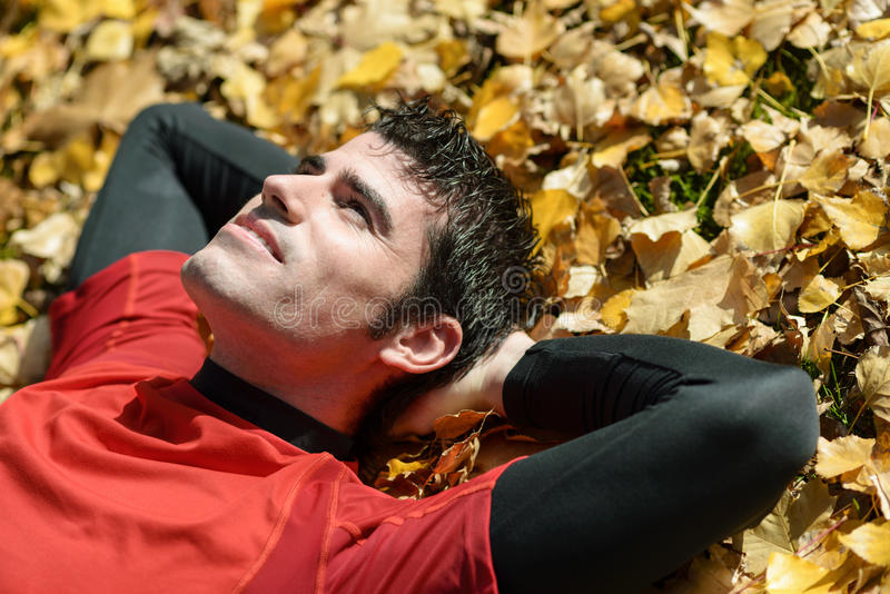 Resting and day dreaming man. Man thinking and day dreaming liyind down on ground outdoors. Sportsman resting stock photography