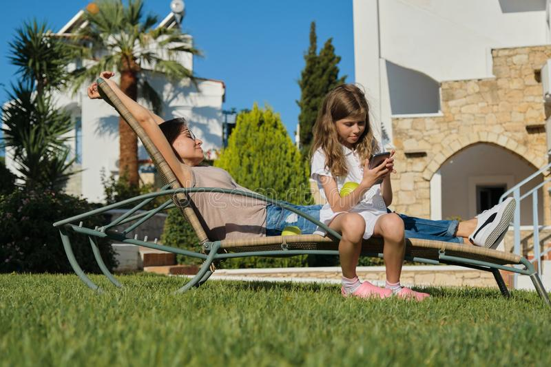 Resting happy family mother and daughter sitting in an outdoor chair stock images