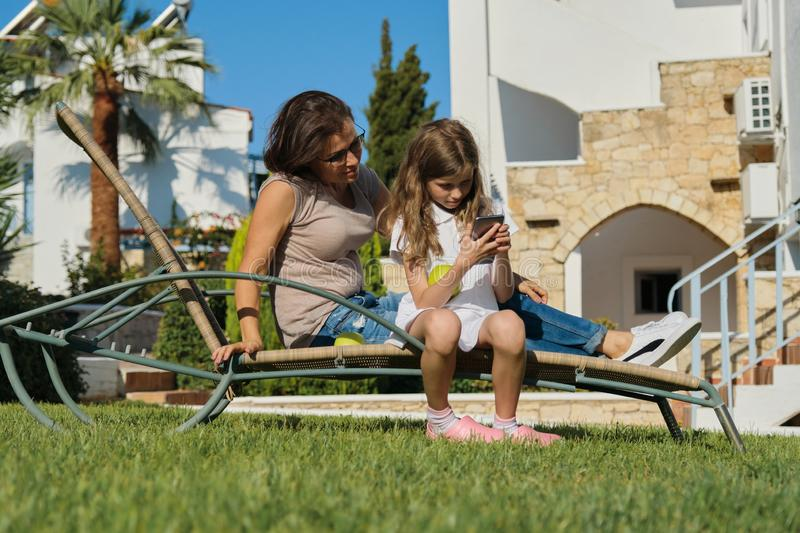 Resting happy family mother and daughter sitting in an outdoor chair stock photography