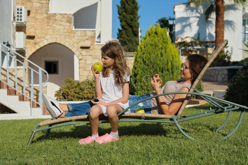 Resting happy family mother and daughter sitting in outdoor chair royalty free stock image
