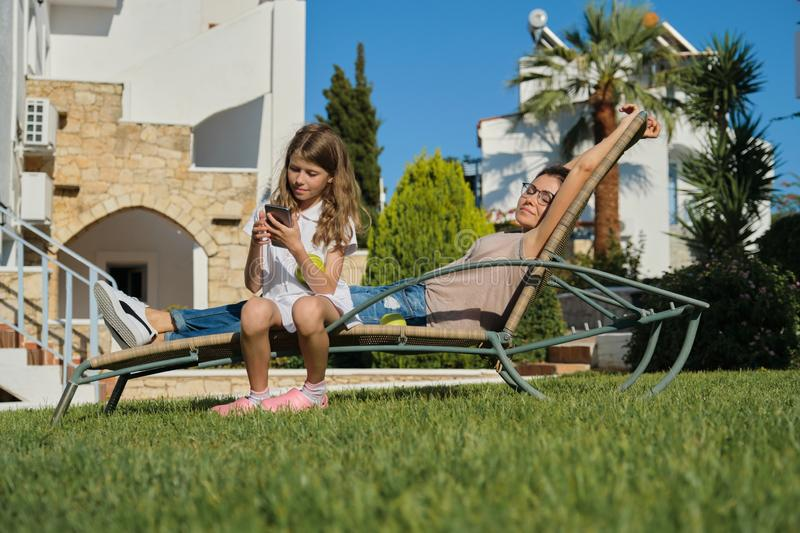 Resting happy family mother and daughter sitting in an outdoor chair royalty free stock photography