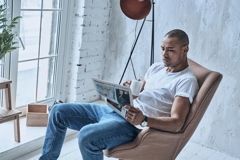 Resting at home. Handsome young African man reading newspaper an royalty free stock images