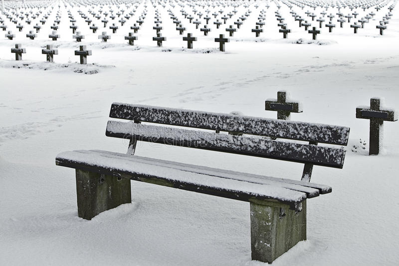 Resting place bench in snow at graveyard royalty free stock photos