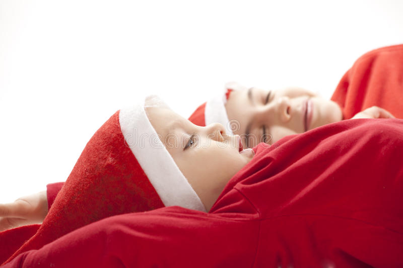 Resting Santas. Portrtait of a girl and boy in christmas hats royalty free stock photos