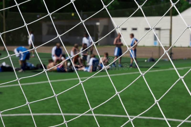 Resting soccer team. look trough goal net. stock photos