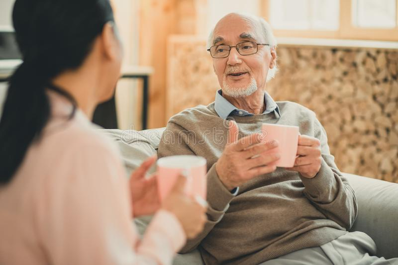Old man having friendly conversation with his female friend. Resting on sofa. Old men having friendly conversation with his female friend on comfy grey couch stock image