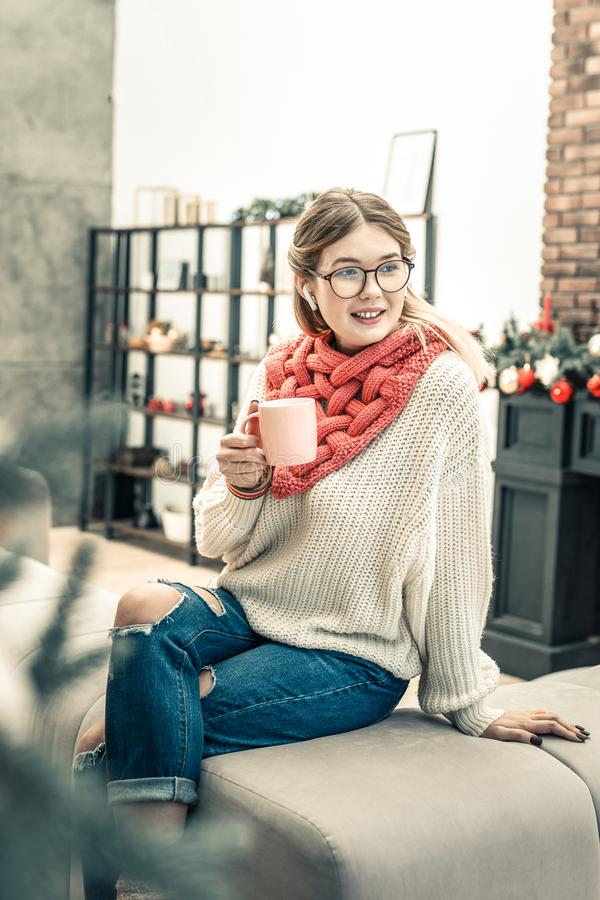 Long-haired lady in clear glasses wearing ragged jeans royalty free stock image